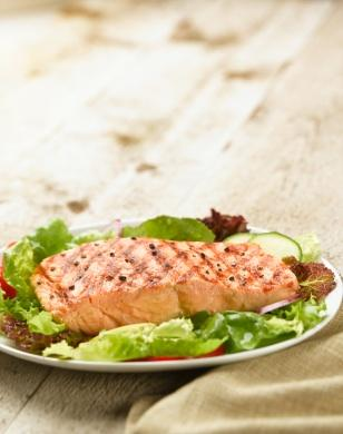 Grilled salmon is accompanied by butter lettuce for a refreshing dinner.