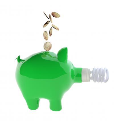 Green piggy bank with fluorescent bulb receiving money
