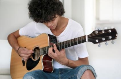 Teenager learning acoustic guitar