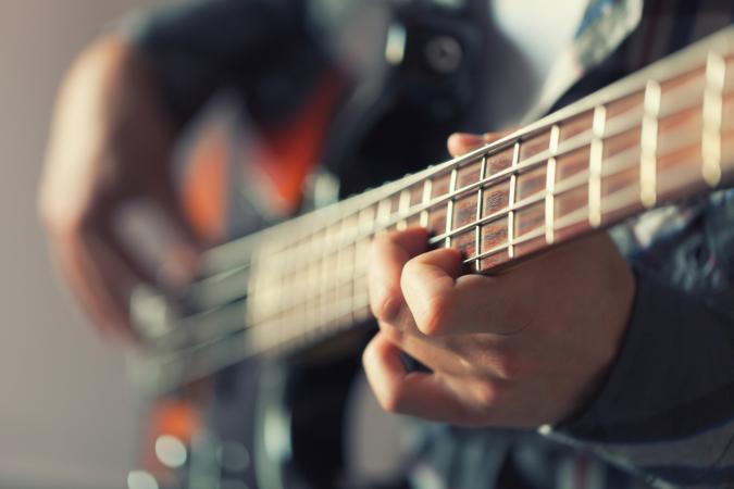 Closeup of man playing bass guitar