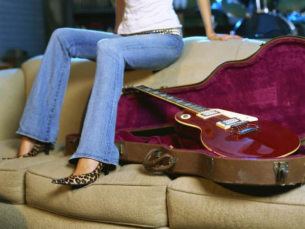 woman sitting near a guitar