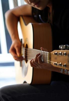 A lone guitarist fingers a chord.