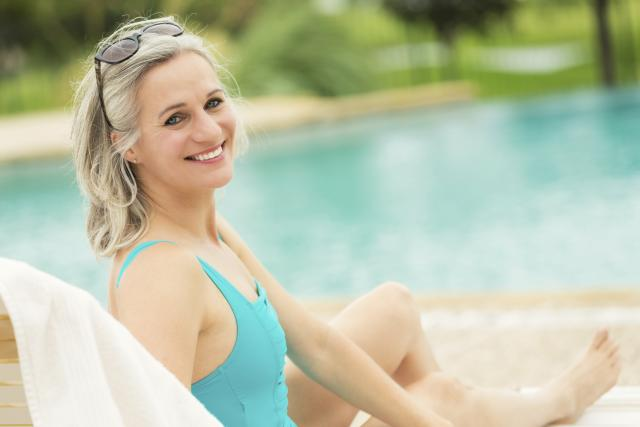 Pretty senior woman relaxes beside swimming pool