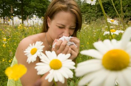 Lady in field of flowers suffering from hay fever
