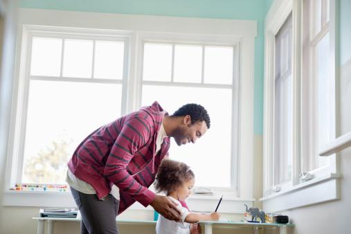 Father assisting daughter with homework