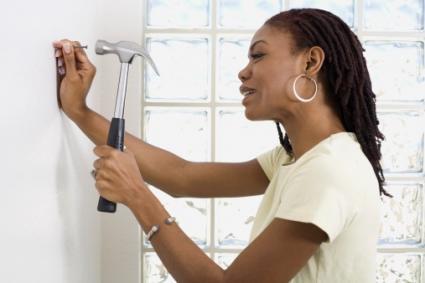 Hammering nail into wall