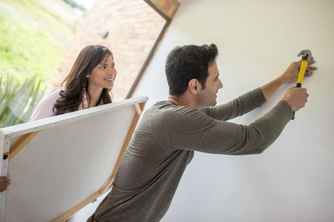 Couple hanging a picture