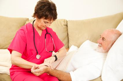Nurse taking patient's pulse while consulting her watch.