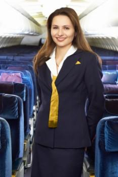 Fight attendant standing in airplane aisle