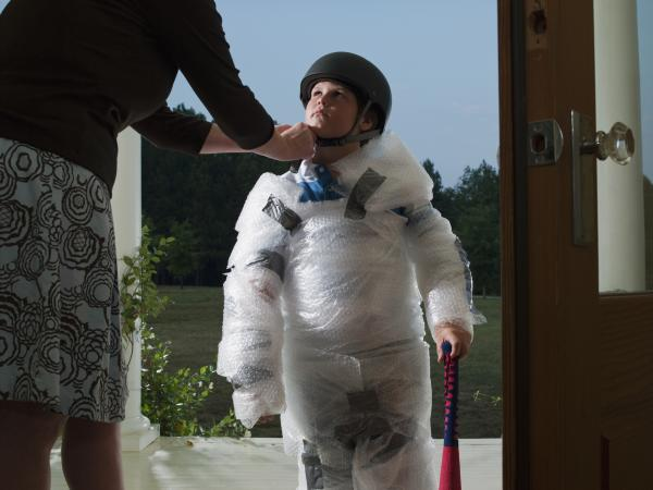 Mother putting helmet on son's head wrapped in bubble wrap