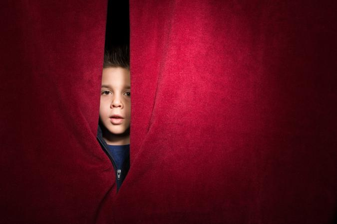Child appearing from behind curtain