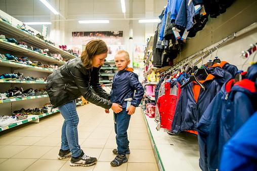 mother and son shopping in clothing store