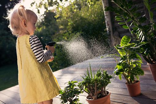 Girl spraying water on plants