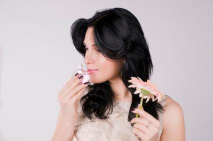 Woman applying perfume.
