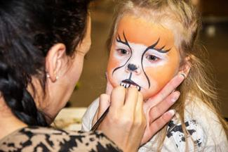 Girl having cat face painted