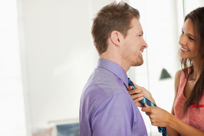 Woman tying husbands necktie