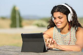 Girl listening to music and sharing it on tablet