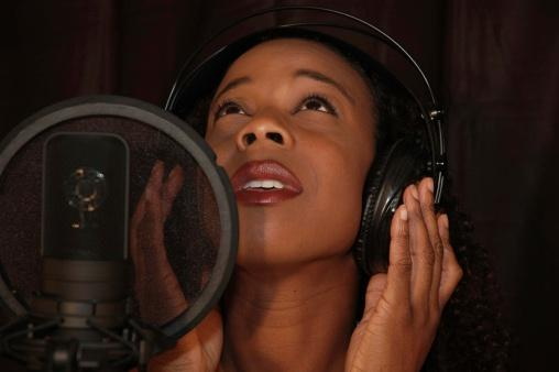Woman singing in a recording booth