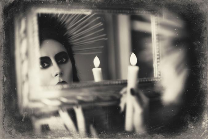 Girl holding candle looking in mirror
