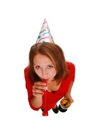 Woman with party hat and noisemaker