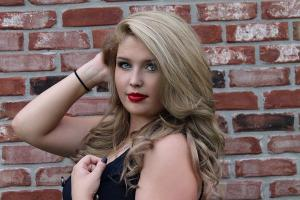 senior photo in front of brick wall