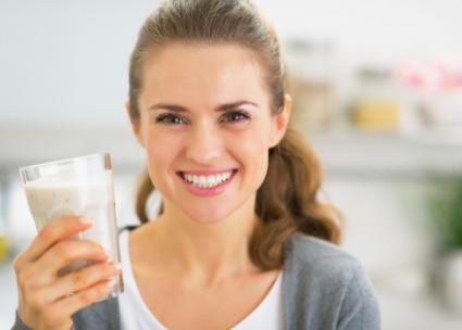 Woman drinking smoothie in kitchen
