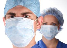 Medical professionals wearing scrubs, caps, and masks.