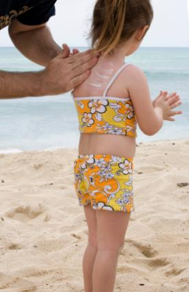 Applying sunscreen to a child's back