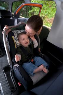 Woman fastening child into carseat