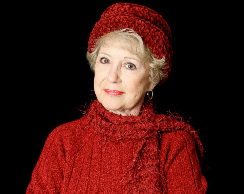 Senior woman wearing a red sweater, hat and scarf.