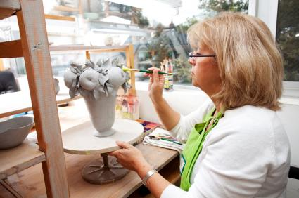 Senior painting a ceramic vase with apples