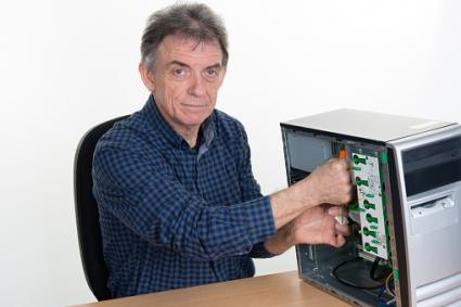Elderly man repairing computer