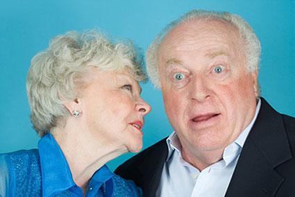 Senior woman whispering to husband