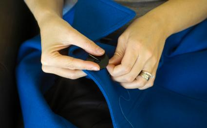 sewing button on a coat