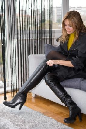 woman putting on knee high boots
