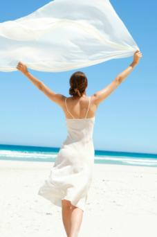 Woman with billowing chiffon on beach