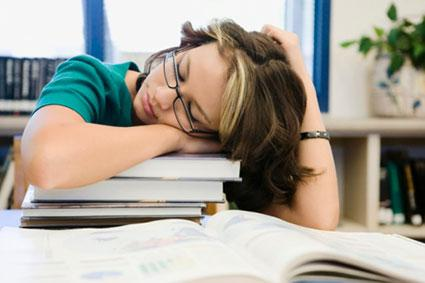 High school student sleeping in library