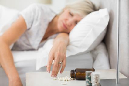 Woman sleeping in bed with pills in foreground