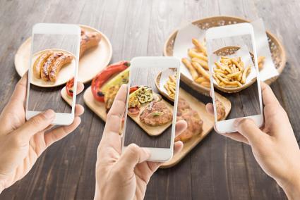 Smartphones taking photos of food