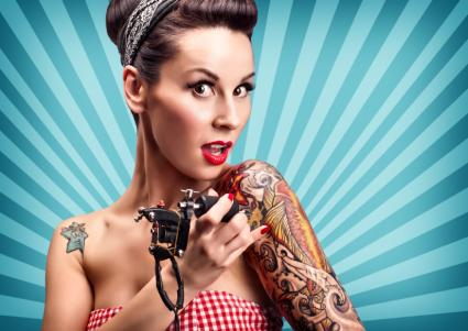 Pinup girl with tattoos and tattoo gun