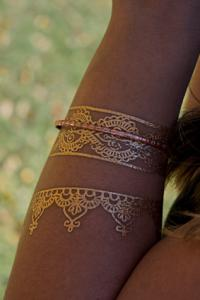 Metallic temporary tattoo on arm