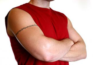 barbed wire tattoo on man with arms crossed