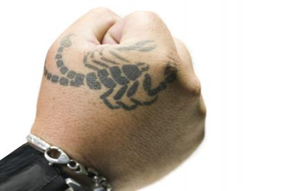 Male fist with scorpion tattoo