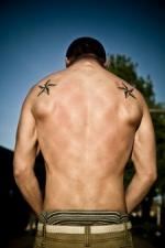 Man with star shoulder tats