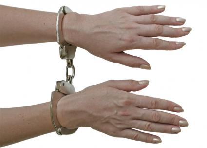 Women's hands in hand cuffs