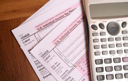 Two tax forms with calculator