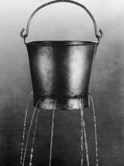 Water poring through holes in bucket