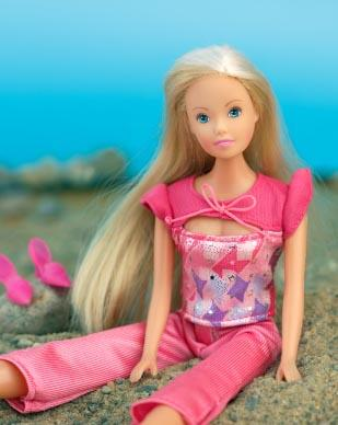 Doll sitting at beach
