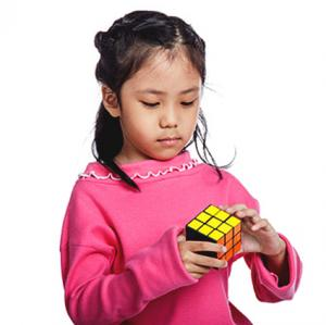 Little girl playing with a Rubik Cube