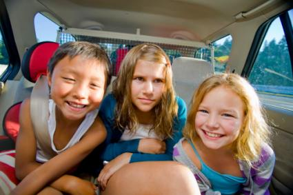 Children making faces in car